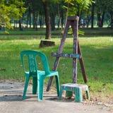 En staffli med två plasstic stolar Royaltyfri Bild
