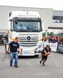 En stark kvinna drar en tung lastbil med ett rep arkivbild