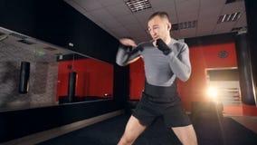 En stark manlig kämpe gör shadowboxing stock video