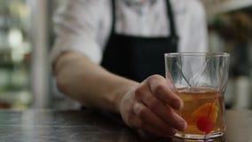 En stark uppassarehand b?r ett brunt magasin med ett exponeringsglas av coctail till kunderna modern cafe Morgontraditioner stock video