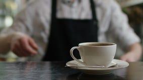 En stark uppassarehand b?r ett brunt magasin med en kopp kaffe till kunderna modern cafe Morgontraditioner Cafe arkivfilmer