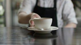 En stark uppassarehand b?r ett brunt magasin med en kopp kaffe till kunderna modern cafe Morgontraditioner Cafe lager videofilmer