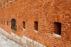 En stark vägg för röd tegelsten som omger en forntida slott- eller antikvitetfästning som befästning royaltyfri foto