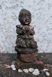 En staty av en flicka som står över en hög av stenar royaltyfri bild