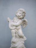 En staty av en kupidon som spelar det klassiska instrumentet Royaltyfria Bilder