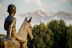 En staty av en pojke som rider en häst och beskådar till snöig berg som täckas litet av moln Arkivfoto