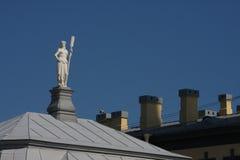 En staty av en flicka med en skovel, ett symbol av den Neva floden, på taket av en av de inre byggnaderna av fästningen Fotografering för Bildbyråer