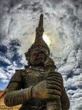 En staty av en krigare som bevakar templet royaltyfria bilder