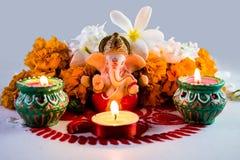 En staty av en mytologisk elefantgud - Ganesha som omges av traditionella divalilampor royaltyfri fotografi
