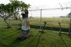 En staty eller en liten hindus tempel med den skugga, bredvid frangipaniträden och det dimmiga fältet på bakgrunden royaltyfri bild