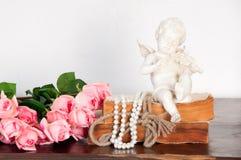 En statyett av en ängel som spelar en fiol, sitter på en bok Royaltyfri Foto
