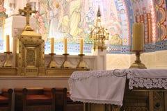 En stearinljus förläggas på ett altare i ett kyrkligt (Frankrike) royaltyfria bilder