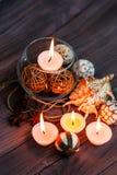 En stearinljus i en glass vas, en garnering och olika intressanta beståndsdelar burning stearinljus Royaltyfria Foton