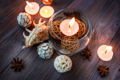 En stearinljus i en glass vas, en garnering och olika intressanta beståndsdelar burning stearinljus Arkivbild
