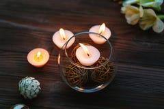 En stearinljus i en glass vas, en garnering och olika intressanta beståndsdelar burning stearinljus Royaltyfri Fotografi