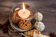 En stearinljus i en glass vas, en garnering och olika intressanta beståndsdelar burning stearinljus Royaltyfria Bilder