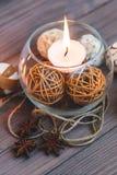 En stearinljus i en glass vas, en garnering och olika intressanta beståndsdelar burning stearinljus Arkivfoto