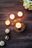 En stearinljus i en glass vas, en garnering och olika intressanta beståndsdelar burning stearinljus Royaltyfri Foto