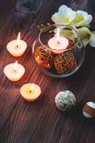 En stearinljus i en glass vas, en garnering och olika intressanta beståndsdelar burning stearinljus Fotografering för Bildbyråer