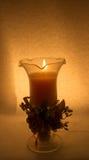 En stearinljus i ett exponeringsglas på en vit bakgrund royaltyfri foto