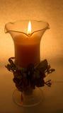 En stearinljus i ett exponeringsglas på en vit bakgrund royaltyfri bild