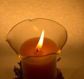 En stearinljus i ett exponeringsglas på en vit bakgrund royaltyfria foton