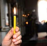 En stearinljus i handen av ett barn arkivfoton