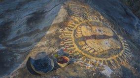 En sten med bilden av fotspåren av en guru överst av A M. royaltyfria bilder