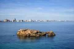 En stenig holme av kusten av La Manga, Spanien fotografering för bildbyråer