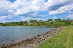 En stenig kust nedanför lilla staden av port Hawkesbury på uddeBretonön royaltyfri bild