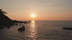 En stenig strand n?ra den Palomem stranden p? solnedg?ngen Goa tillst?nd india stock video