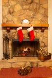 En stenspis med två julstrumpor hängde på ansvaret och familjkatten som kopplar av vid branden royaltyfri fotografi