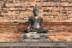 En stenstaty av Buddha installerades framme av en tegelstenvägg i en parkera i Sukhothai (Thailand) Arkivbild