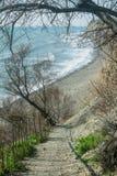 En stentrappuppgång på en brant berglutning ovanför havet arkivbild