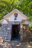 En stenvägg av en liten byggnad med enmonterad sockel av en framsida för man` s på ingången arkivbild
