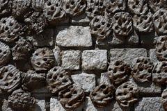 En stenvägg som göras av massiva gråa tegelstenar, med fastnade kakor av gödsel av kor, tankar för ugnar Royaltyfria Foton