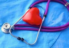 En stetoskop som formar en hjärta och en skrivplatta på a Royaltyfria Bilder