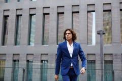 En stilfull blått för stilig affärsman passar bråttom för ett möte royaltyfri foto
