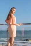 En stilfull dam på en terrass för sommarhotell` s Den härliga flickan i en rosa klänning nära ett hav Damen på en ljus solig bakg royaltyfri fotografi