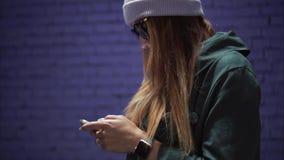 En stilfull hipsterflicka i trendiga exponeringsglas och en hatt genom att använda app på smartphonen nära en tegelstenvioletvägg royaltyfri foto