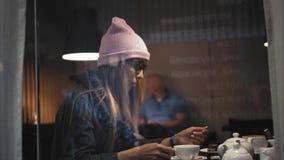 En stilfull hipsterkvinnlig i exponeringsglas genom att använda den smarta klockan och genom att använda app på en smartphone i e royaltyfri bild