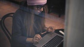 En stilfull hipsterkvinnlig i exponeringsglas och hattmaskinskrivning på en bärbar dator i ett kafé Bästa sikt till och med fönst royaltyfri fotografi