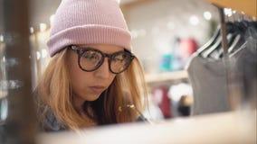 En stilfull hipsterkvinnlig kommer till lagerkuggen och väljer nya exponeringsglas _ fotografering för bildbyråer