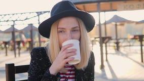 En stilfull kvinna i en hatt dricker kaffe i ett kafé i parkerar Hon ler, kommer med en kopp med en drink till hennes mun lager videofilmer