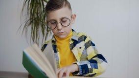 En stilfull liten elev i exponeringsglas med blåa ögon utför en hemmastadd läsning för läxa en rolig bok Skolpojken läser a stock video