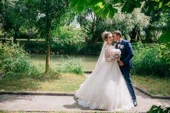 En stilfull man i en dräkt i en bur kramar hans älskling och begraver hans framsida i hennes blonda hår Bruden i en ursnygg klänn fotografering för bildbyråer