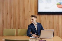 En stilfull man i ett omslag och en skjorta sitter p? skrivbordet med hans kollegor och arbeten med dokument p? kontoret arkivfoton