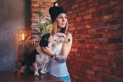 En stilfull tattoed blond kvinnlig i t-skjorta och jeans omfamnar två gulliga hundkapplöpning Royaltyfri Bild