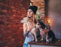 En stilfull tattoed blond kvinnlig i t-skjorta och jeans omfamnar två gulliga hundkapplöpning Royaltyfria Foton