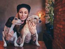 En stilfull tattoed blond kvinnlig i t-skjorta och jeans omfamnar två gulliga hundkapplöpning Arkivfoto
